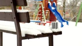 Handen die hete drank in witte zwarte gestreepte kop van thermosflessen in een de winterpark voorbereiden Verse poedersneeuw op h stock footage