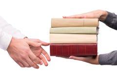 Handen die hoop van boeken overgaan Stock Foto's