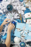 Handen die Kerstboom verfraaien Stock Afbeeldingen