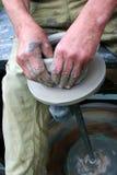 Handen die klei op het wiel van de pottenbakker vormen Stock Fotografie