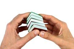Handen die kleine miniatuurdieboeken houden, op wit worden geïsoleerd Royalty-vrije Stock Afbeelding