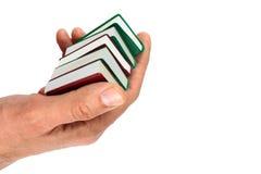Handen die kleine miniatuurdieboeken houden, op wit worden geïsoleerd Stock Afbeeldingen