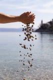Handen die kleine stenen in het overzees laten vallen Stock Foto's
