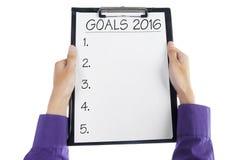 Handen die klembord houden om bedrijfsdoelstellingen in 2016 te maken Stock Foto's