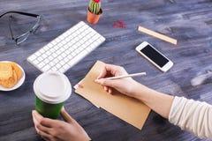 Handen die koffie en het schrijven houden Stock Afbeeldingen