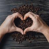 Handen die koffiebonen in vorm van hart houden Stock Afbeelding