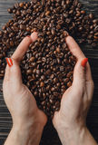 Handen die koffiebonen in vorm van hart houden Stock Afbeeldingen
