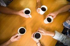 Handen die koffiemokken op lijst houden Royalty-vrije Stock Afbeeldingen