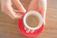 Handen die kop van hete koffie houden Stock Foto