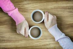 Handen die koppen van koffie houden op houten lijst heet Stock Fotografie