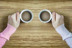 Handen die koppen van koffie houden op houten lijst heet Royalty-vrije Stock Foto