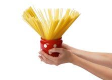 Handen die kruik met binnen spaghetti houden Stock Foto's