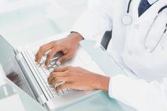 Handen die laptop met behulp van op medisch kantoor Stock Fotografie