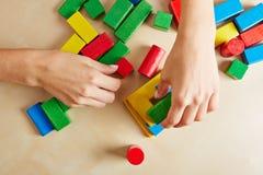 Handen die met bouwstenen spelen Stock Foto's