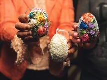 Handen die moderne geschilderde paaseieren houden royalty-vrije stock foto's