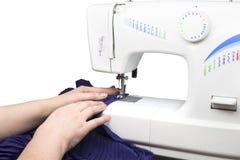 Handen die naaimachine met behulp van Stock Foto