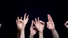 Handen die O.k. of flicking teken maken O.k. die codage met de hand op zwarte achtergrond wordt geïsoleerd De handen tonen gebaar stock footage