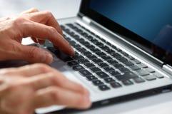 Handen die op laptop computer typen Stock Afbeeldingen