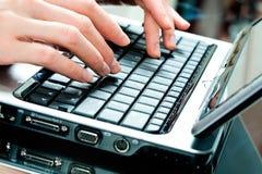 Handen die op laptop typen Stock Foto