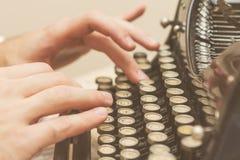 Handen die op oude schrijfmachine schrijven Stock Foto