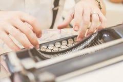 Handen die op oude schrijfmachine schrijven Stock Foto's