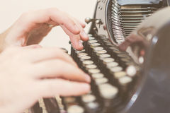 Handen die op oude schrijfmachine schrijven Stock Afbeeldingen