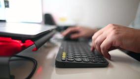 Handen die op toetsenbord met bureaupunten en laptop in kader typen stock footage