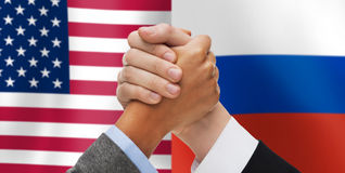 Handen die over Amerikaanse en Russische vlaggen armwrestling Stock Foto