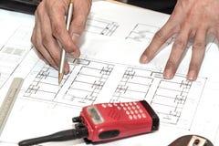 Handen die penpunt houden aan de architecturale tekening van het plannenproject Stock Foto