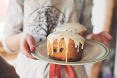 Handen die plaat met eigengemaakte Pasen-cake houden kulich - wit suikerglazuur Zachte nadruk Stock Foto's