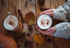Handen die pompoenkruid latte in glaskop houden, op houten achtergrond, hoogste mening stock afbeelding