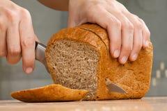 Handen die roggebrood snijden Stock Afbeelding