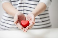 Handen die rood hart, valentijnskaartfestival en veiligheidsconcept geven stock fotografie