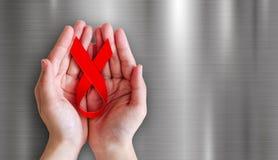 Handen die rood lint op metaalachtergrond houden voor de dag van de wereldhulp Stock Afbeelding