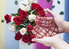 Handen die rood metaalhart met rozenachtergrond houden Royalty-vrije Stock Foto's