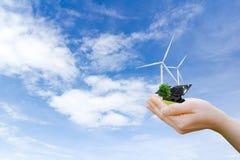 Handen die schone de windturbine van de boomelektrische energie en zonnecel houden de toekomst stock afbeelding