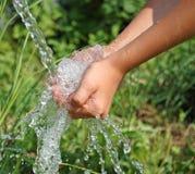Handen die schoon dalend water dicht inhalen