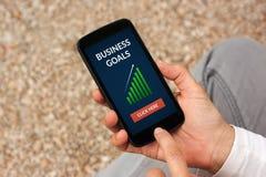 Handen die slimme telefoon met bedrijfsdoelstellingen concept op het scherm houden Royalty-vrije Stock Foto's