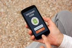 Handen die slimme telefoon met het concept van de kortingscode op het scherm houden royalty-vrije stock foto's