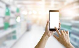 Handen die slimme telefoon in supermarkt voor het winkelen met behulp van stock fotografie