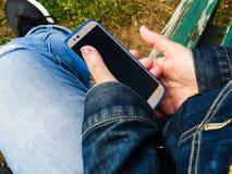 Handen die Smartphone houden terwijl het Zitten op Bank het Ontspannen royalty-vrije stock afbeeldingen