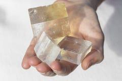 Handen die stuk van Optisch Kalkspaat houden stock foto