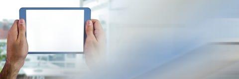 Handen die tablet houden tegen de onscherpe bouw met onscherpe blauwe en grijze overgang Stock Afbeelding