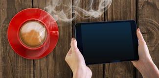 Handen die tablet meer dan een kop van koffie houden Royalty-vrije Stock Afbeelding