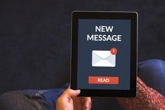 Handen die tabletcomputer met nieuw berichtconcept houden op het scherm Stock Foto's