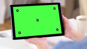 Handen die tabletpc met het groene scherm thuis houden stock videobeelden