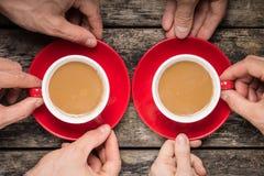 Handen die Twee Rode Koppen van Koffie op oude Houten Achtergrond nemen Royalty-vrije Stock Afbeeldingen