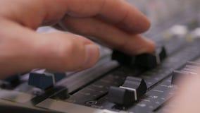 Handen die van Audioingenieur aan een professionele analoge console, het bewegen zich faders werken, die muziek mengen stock video