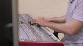Handen die van Audioingenieur aan een professionele analoge console, het bewegen zich faders werken, die muziek mengen stock videobeelden