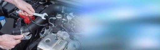 Handen die van autowerktuigkundige aan motor van een auto werken Stock Foto's